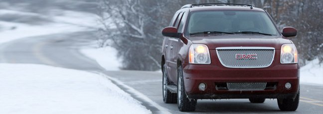 Red GMC SUV driving in the snow.