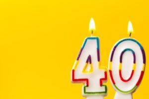 Number 40 in white birthday candles against a yellow background