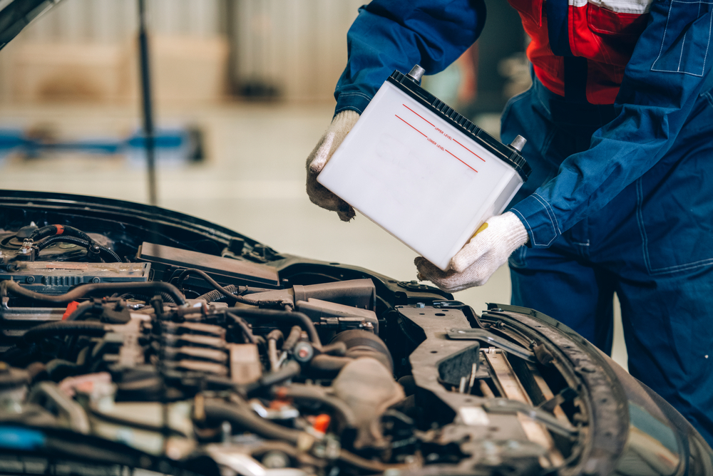 Male mechanic changing car battery, engineer is replacing car battery because car battery is depleted