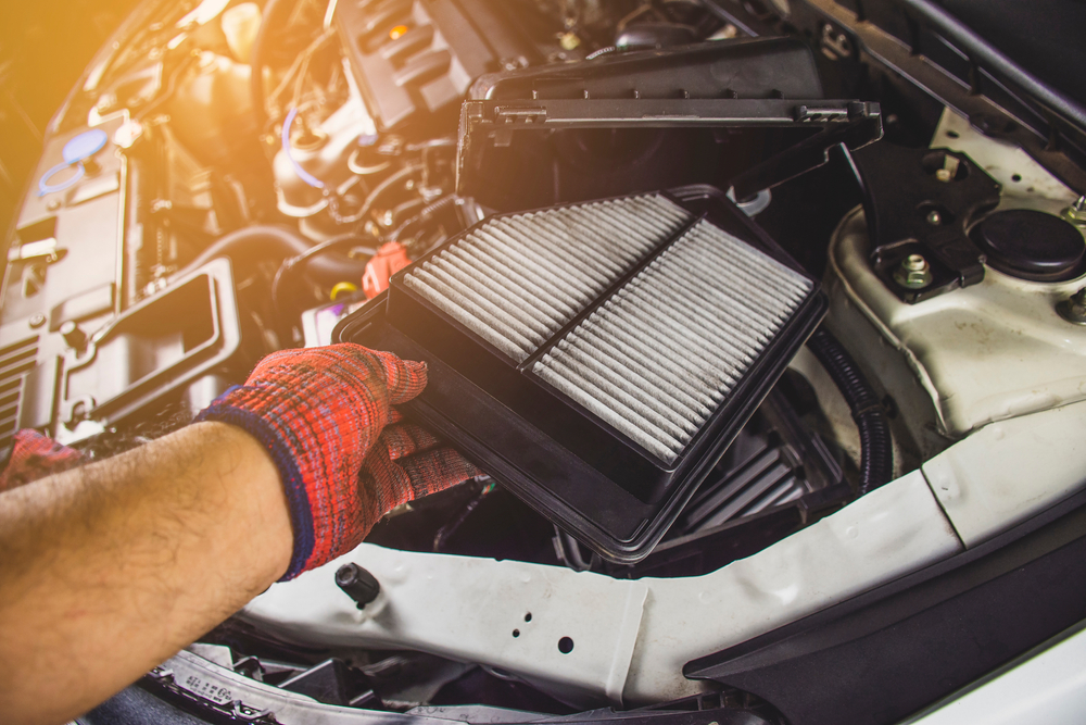 mechanic removing dirty air filter from car